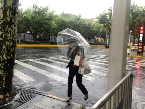 A woman carrying an umbrella braces against the wind and rain as Typhoon In-fa sweeps through Shanghai (AP)