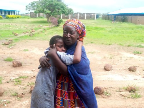 A parent is reunited with a released student at the Bethel Baptist High School in Damishi (AP)