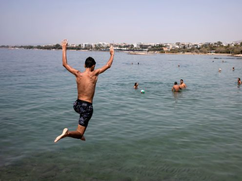 A youth jumps in the sea at a beach of Kavouri suburb, south-west of Athens (Yorgos Karahalis/AP)