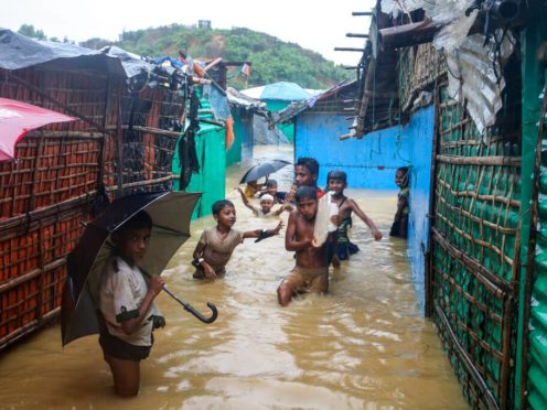 Children play in floodwaters at a Rohingya refugee camp (Shafiqur Rahman/AP)