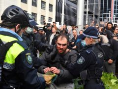 A protester (centre) is arrested by police at a demonstration at Sydney Town Hall (Mick Tsikas/AAP Image via AP/PA)