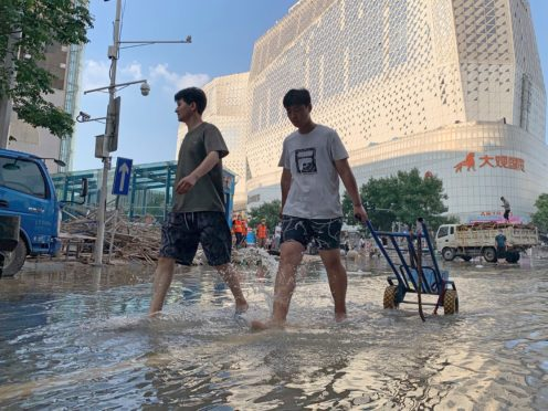 Residents walk along a flooded road in the aftermath of the heaviest recorded rainfall in Zhengzhou (Dake Kang/AP/PA)