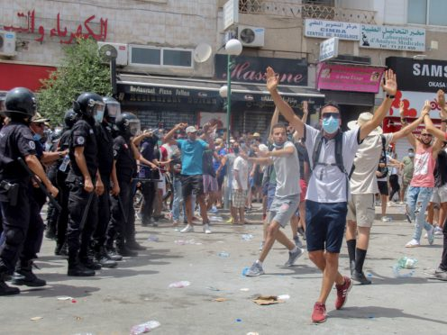 Protesters face Tunisian police officers during a demonstration in Tunis (Hassene Dridi/AP)