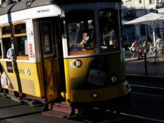 A tram conductor wearing a face mask drives through Lisbon's Graca neighbourhood (Armando Franca/AP)