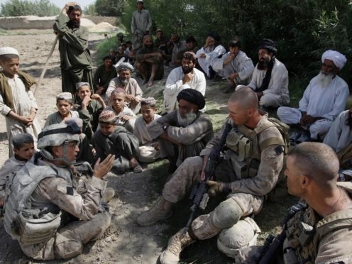 A translator for US Marines speaks with Afghan villagers in Helmand province (David Guttenfelder/AP)