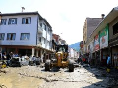 Workers clear the mud from a street in Bozkurt (AP)