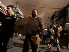 An Israeli soldier carries a box of sandwiches as he walks with a fellow soldier through the Machane Yehuda market under a sky darkened by nearby wildfires, in Jerusalem (Maya Alleruzzo/AP)