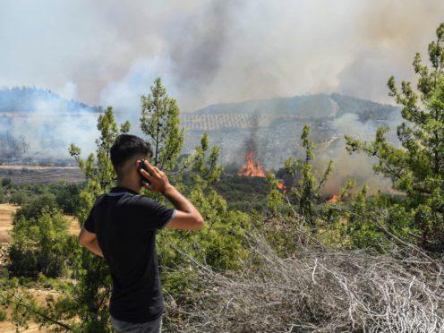 A man watches wildfires in Antalya, Turkey (AP)