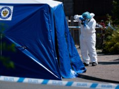 A forensics officer takes photographs at the scene of the stabbing on College Road, Kingstanding (Jacob King/PA)