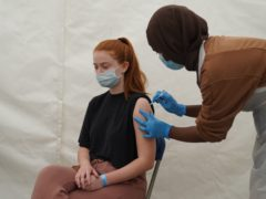 A girl receives a Covid-19 jab at a pop-up vaccination centre during a four-day vaccine festival in east London (Kirsty O'Connor/PA)