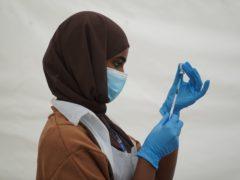 An NHS worker prepares a Covid jab (PA)