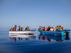 A group await on board precarious wooden boats around 20 miles southwest from the Italian island of Lampedusa (Santi Palacios/AP)