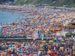 A packed Bournemouth beach during last month's heatwave. The UK is on track to record one of its 10 hottest summers (Ben Birchall/PA)