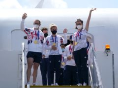 Great Britain's Jason and Laura Kenny and Katie Archibald wave as they arrive at Heathrow Airport (Steve PArsons/PA)