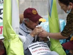 A Gurkha veteran drinks water during a hunger strike opposite Downing Street in London (Hollie Adams/PA)