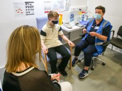 Denise O'Mahony McKeon with her son Kevin Mckeon, 14, as she speaks to vaccinator Geraldine Flynn before he receives his first dose of the Covid-19 vaccine at the Citywest vaccination centre in Dublin (Damien Storan/PA)