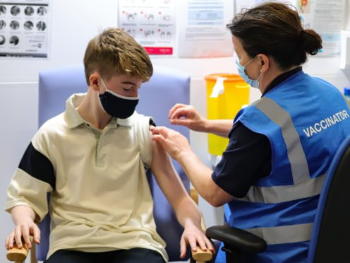 Kevin Mckeon, 14, receives his first dose of the Covid-19 (PA)