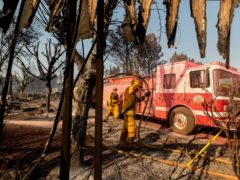 Firefighters mop up at Cache Creek Mobile Home Estates where the Cache Fire levelled dozens of residences (Noah Berger/AP)