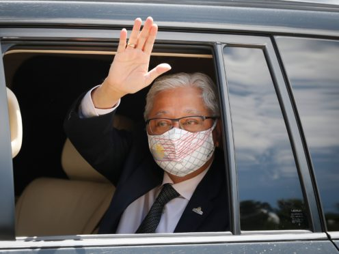 Former deputy prime minister Ismail Sabri Yaakob waves as he leave after meeting with the King at the national palace in Kuala Lumpur, Malaysia (FL Wong/AP)