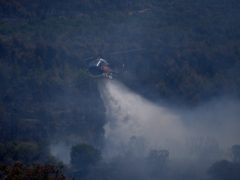 An helicopter drops water on a wildfire near Le Luc, southern France (Daniel Cole/PA)