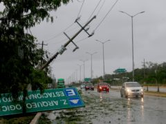 A road sign brought down by the winds of Hurricane Grace lays on the side of the highway in Tulum, Quintana Roo state, Mexico, Thursday, Aug. 19, 2021. The Category 1 storm made landfall at 4:45 a.m., just south of the ancient Mayan temples of Tulum, pelting the Caribbean coast with heavy rain and pushing a dangerous storm surge. (AP Photo/Marco Ugarte)