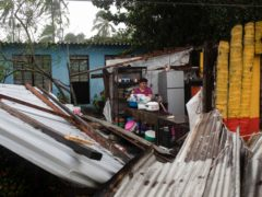 A woman begins clearing debris from her kitchen after a part of her home was damaged by winds brought on by Hurricane Grace, in Tecolutla, Veracruz State, Mexico, on Saturday (Felix Marquez/AP)
