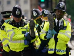 Police remove a demonstrator during a protest by members of Extinction Rebellion on Whitehall in London (Yui Mok/PA)