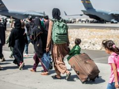 Families walk towards their flight during ongoing evacuations at Hamid Karzai International Airport, Kabul, Afghanistan (Sgt Samuel Ruiz/US Marine Corps via AP)