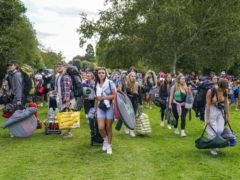 Festivalgoers walk along the towpath of the River Thames as they arrive for the Reading Festival (Steve Parsons/PA)