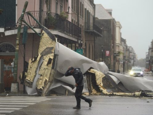 A man passes by a section of roof that was blown off of a building in the French Quarter by Hurricane Ida winds in New Orleans (Eric Gay/AP)