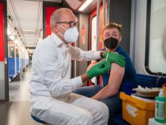 Christian Gravert, chief medical officer of the Deutsche Bahn, vaccinates a man with the Johnson & Johnson vaccine in a special train of the public transport S-Bahn, in which vaccination against Covid-19 are offered, in Berlin, Germany (Christophe Gateau/dpa via AP)