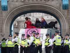 Police by a caravan on Tower Bridge, central London after members of Extinction Rebellion blocked the road (Stefan Rousseau/PA)