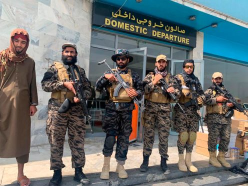 Taliban fighters stand guard inside the Hamid Karzai International Airport (AP)