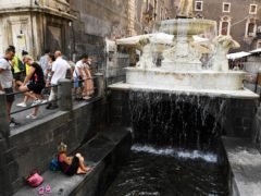 A woman sits near a fountain in a street of Catania, Sicily (Salvatore Cavalli/AP)