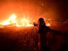 A man uses a water hose during a wildfire in Adames area, in northern Athens, Greece (Michael Varaklas/AP)