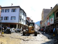 Workers clear mud from a street in the town of Bozkurt after floods brought chaos and destruction (AP)