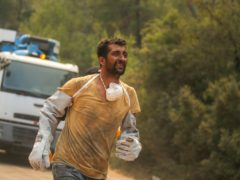 A Turkish volunteer runs as they head to fight wildfires in Turgut village (AP)