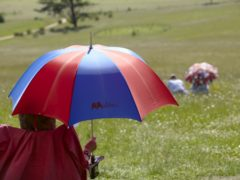 Visitors sitting at Croome Park, Worcestershire, using an umbrella as a sun shade (National Trust/PA)