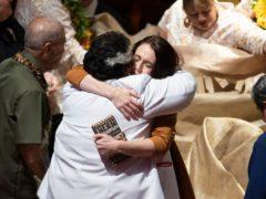 Jacinda Ardern is hugged during a ceremony in Auckland (Brett Phibbs/New Zealand Herald via AP)
