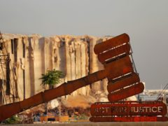A justice symbol monument is seen in front of towering grain silos that were gutted in the massive August 2020 explosion at the port that claimed the lives of more than 200 people, in Beirut, Lebanon (Hussein Malla/AP)