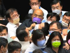 Premier Su Tseng-chang, in purple mask, tries to make a policy speech amid a scuffle between opposition Nationalist party and ruling Democratic Progressive Party lawmakers (EBC/AP)