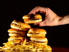 A pile of cheeseburgers and chips (Dominic Lipinski/PA)