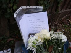 Floral tributes and a card left outside Highdown School in Reading after Olly's murder (PA)
