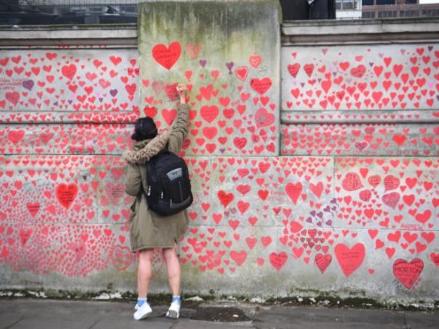 A woman writes in a heart on the Covid memorial wall on the Embankment in London (Victoria Jones/PA)