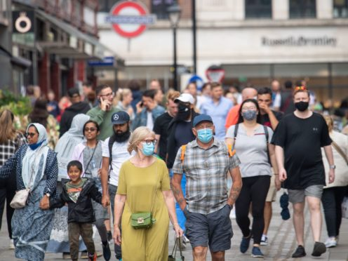 People wearing face masks among crowds of pedestrians in Covent Garden, London (Dominic Lipinski/PA)