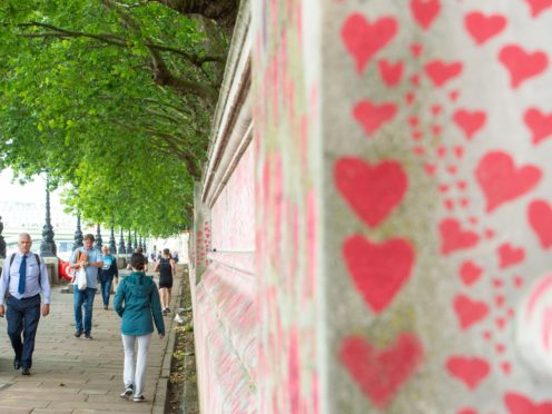 Pedestrians walk past the Covid memorial wall in Westminster, London (Dominic Lipinski/PA)