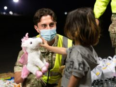 Military personnel handing out food, drink, toys, and blankets during Operation Pitting at RAF Brize Norton (Cpl Will Drummee RAF/MOD/Crown copyright)