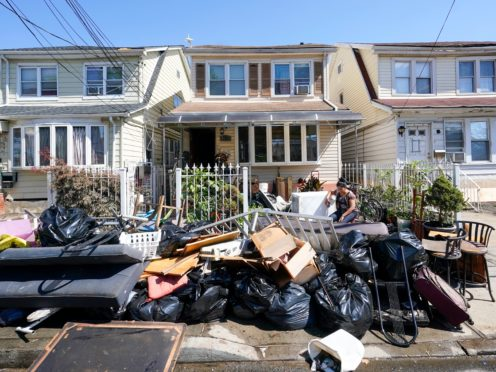 A woman sits next to her drenched belongings (Mary Altaffer/AP)