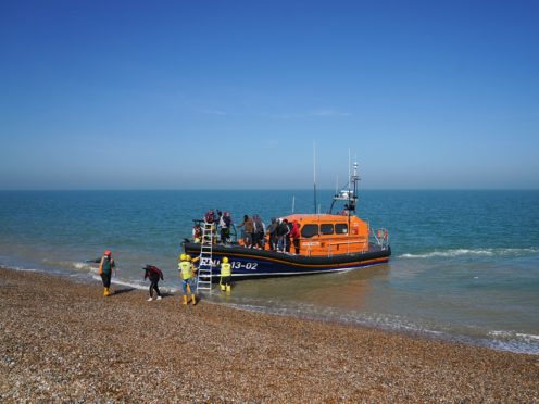 A group of people thought to be migrants are brought ashore from the local lifeboat at Dungeness in Kent (Gareth Fuller/PA)