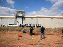 Police officers and prison guards inspect the scene of an escape (Sebastian Scheiner/AP)